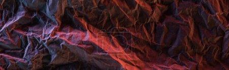 Panoramaaufnahme aus zerknülltem Papier mit rosa und roter farbiger Beleuchtung in der Dunkelheit