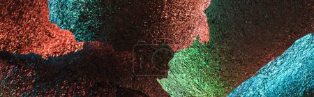 panoramic shot of abstract background of silver textured foil pieces with colorful illumination