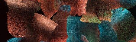 Photo pour Tir panoramique de fond abstrait de papier d'aluminium en lambeaux avec l'illumination colorée d'isolement sur le noir - image libre de droit