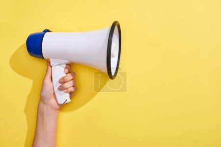 Photo for Cropped view of woman holding loudspeaker on yellow background - Royalty Free Image