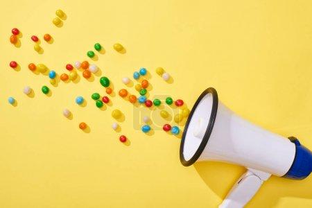 Photo pour Vue du haut-parleur avec des bonbons colorés sur fond jaune - image libre de droit