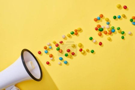 Photo for Top view of loudspeaker with colorful candies on yellow background - Royalty Free Image