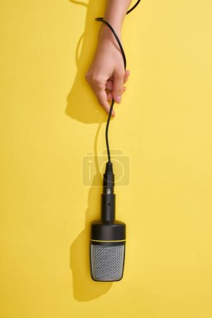 Photo pour Vue recadrée de femme retenant le microphone sur le fond jaune - image libre de droit