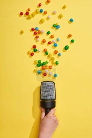 Photo pour Vue recadrée de la femme retenant le microphone avec les bonbons colorés sur le fond jaune - image libre de droit