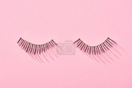 Photo for Top view of false eyelashes on pink background with copy space - Royalty Free Image
