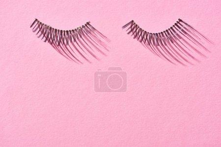 Foto de Top view of false eyelashes on pink background with copy space - Imagen libre de derechos
