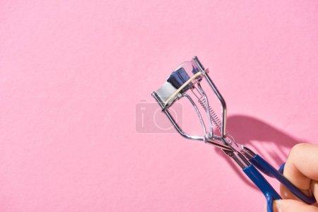 Photo pour Vue recadrée de la femme tenant friseur de cils sur fond rose - image libre de droit
