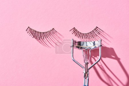 Photo for Top view of false eyelashes and eyelash curler on pink background - Royalty Free Image