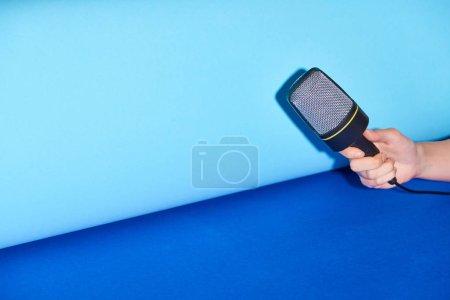 Photo pour Vue recadrée de femme retenant le microphone sur le fond turquoise - image libre de droit