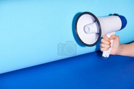 Photo pour Vue recadrée de femme retenant le haut-parleur sur le fond turquoise - image libre de droit