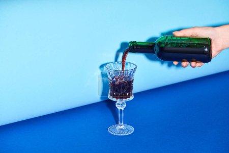Foto de Cropped view of woman pouring wine from bottle to glass - Imagen libre de derechos