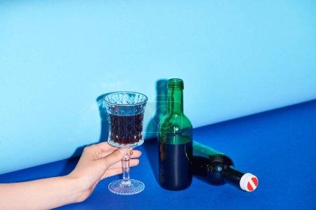 Photo pour Vue recadrée de femme tenant verre avec du vin sur fond coloré - image libre de droit