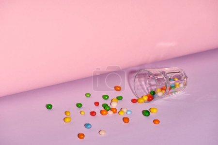 Foto de Vidrio con caramelos dulces sobre fondo brillante y colorido - Imagen libre de derechos
