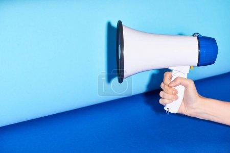 Photo pour Vue recadrée de la femme tenant haut-parleur sur fond turquoise - image libre de droit