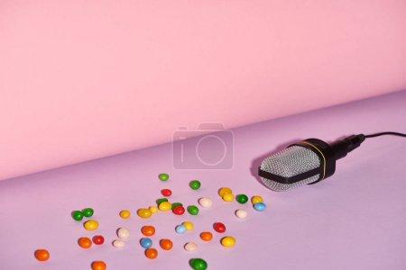 Photo pour Microphone noir avec des bonbons sur le fond lumineux et coloré avec l'espace de copie - image libre de droit