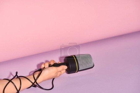 Photo pour Vue recadrée de femme retenant le haut-parleur sur le fond coloré - image libre de droit