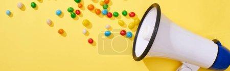 Photo pour Plan panoramique de haut-parleur avec des bonbons sur fond lumineux et coloré - image libre de droit