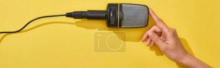 Photo pour Tir panoramique de la femme retenant le microphone sur le fond jaune - image libre de droit