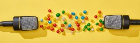 Photo pour Coup panoramique de microphones et de bonbons sur fond lumineux et coloré - image libre de droit