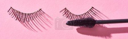 panoramic shot of brush for mascara and false eyelashes on pink background