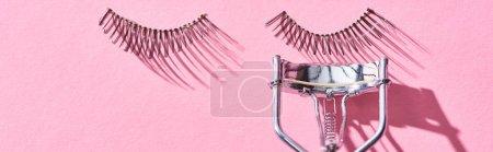 panoramic shot of false eyelashes and eyelash curler on pink background