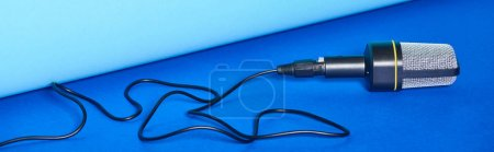 Photo pour Tir panoramique de microphone noir avec le fil sur le fond coloré - image libre de droit
