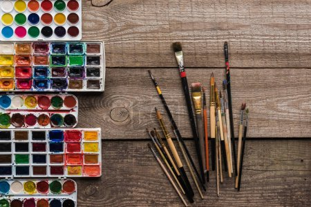 Photo for Top view of colorful paint palettes on wooden brown surface with paintbrushes - Royalty Free Image