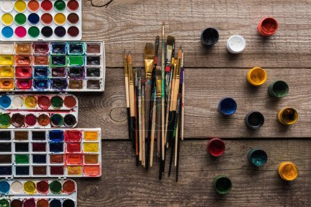 Photo for Top view of colorful paint palettes on wooden brown surface with paintbrushes and gouache - Royalty Free Image