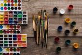 """Постер, картина, фотообои """"верхний вид красочных палитр краски на деревянной коричневой поверхности с кистями и гуашью"""""""