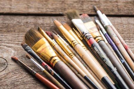 Photo pour Vue rapprochée des pinceaux vieillis sur la surface brun bois - image libre de droit