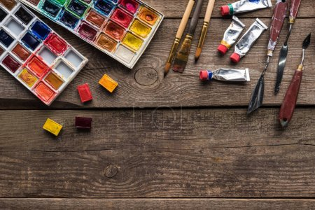 Photo for Top view of colorful paint palettes and drawing tools on wooden surface with copy space - Royalty Free Image