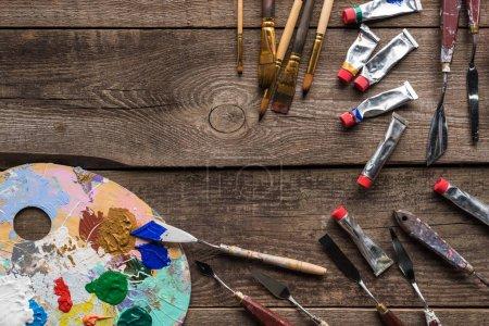 vista superior de la paleta de colores con pinturas y herramientas de dibujo en la superficie de madera con espacio de copia