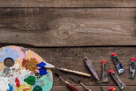 vista superior de la paleta con pinturas al óleo multicolores y herramientas de dibujo en la superficie de madera con espacio de copia