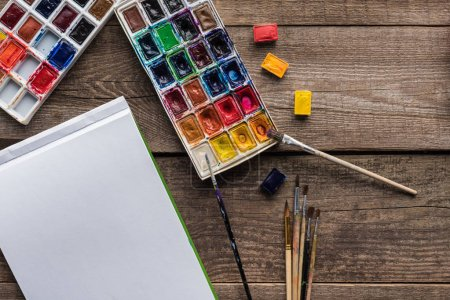 Photo for Top view of colorful paint palettes, paintbrushes and blank sketch pad on wooden surface - Royalty Free Image