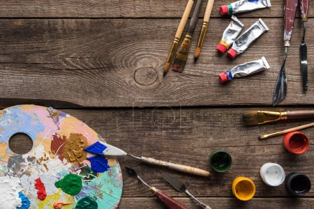 Photo for Top view of drawing tools and color palette on wooden surface with copy space - Royalty Free Image