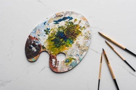 Draufsicht auf bunte Palette mit Ölfarben in der Nähe von Pinseln auf marmorweißer Oberfläche