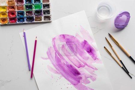 Photo pour Vue supérieure des coups de pinceau violets d'aquarelle sur le papier blanc près des brosses à peinture et des peintures sur la surface blanche de marbre - image libre de droit