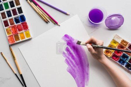 Foto de Vista recortada del artista dibujando pinceladas de acuarela púrpura sobre papel blanco sobre la superficie blanca de mármol - Imagen libre de derechos