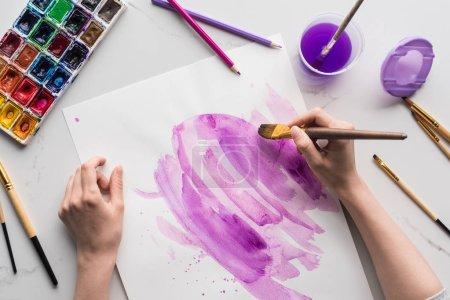 Foto de Vista parcial del artista dibujando pinceladas de acuarela púrpura sobre papel blanco sobre la superficie blanca de mármol - Imagen libre de derechos