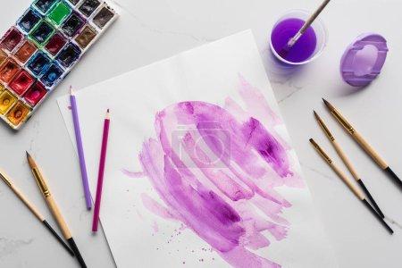 Foto de Vista superior de pinceladas de acuarela púrpura sobre papel blanco cerca de pinceles, pinturas y lápices de colores en la superficie blanca de mármol - Imagen libre de derechos