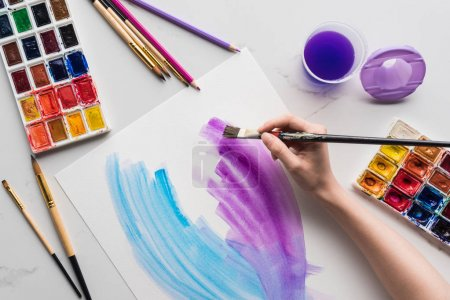 Photo for Cropped view of artist drawing purple and blue watercolor brushstrokes on white paper on marble white surface - Royalty Free Image
