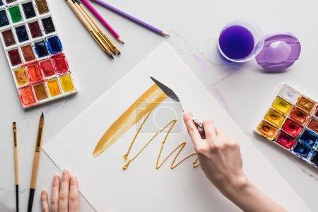 Photo pour Vue partielle du dessin avec spatule sur papier blanc près des pinceaux sur la surface en marbre blanc - image libre de droit