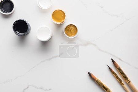 Foto de Vista superior de pinturas de gouache negro, blanco y dorado y pinceles en superficie blanca de mármol con espacio de copia - Imagen libre de derechos
