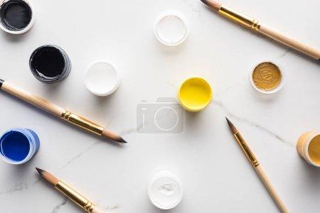 Foto de Vista superior de pinturas de gouache de colores y pinceles dispersos en la superficie blanca de mármol - Imagen libre de derechos