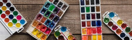 Photo for Top view of colorful paint palettes on wooden brown surface with gouache, panoramic shot - Royalty Free Image