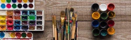 vista superior de coloridas paletas de pintura sobre superficie marrón madera con pinceles y gouache, plano panorámico