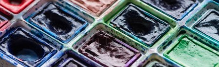 Photo for Close up view of watercolor dirty colorful paint palette, panoramic shot - Royalty Free Image