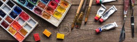 Photo pour Vue de dessus des palettes de peinture colorées et des outils de dessin sur la surface en bois, vue panoramique - image libre de droit