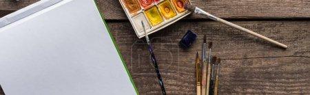 vista superior de la paleta de pintura de colores, pinceles y bloc de bocetos en blanco en la superficie de madera, plano panorámico