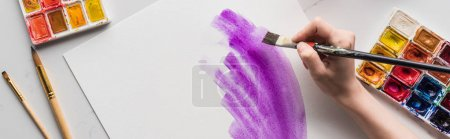 Photo for Cropped view of artist drawing purple watercolor brushstrokes on white paper on marble white surface, panoramic shot - Royalty Free Image